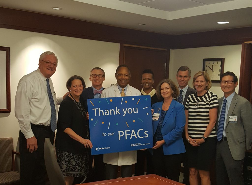 "Duke Health senior leaders pose with a ""Thank You to our Patient and Family Advisory Councils"" poster"