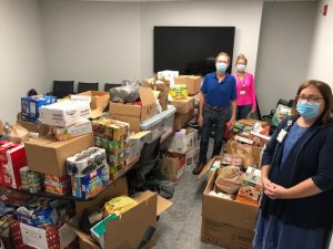 Patient and Family Volunteers and Duke staff members pose with food drive donations
